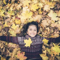 Autumn Garden: Boy playing in leaves