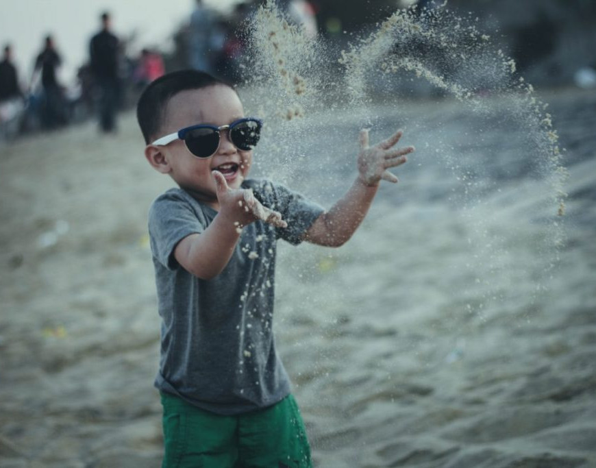 Boy with sunglasses playing on the beach