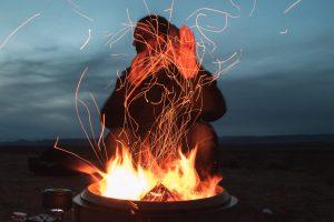 man sitting facing fire in pot during night
